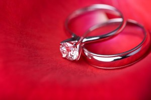 iStock_000004638285Small two wedding rings on red